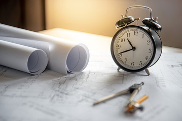 Clock and compass tool on architectural drawing plan of house project, blueprint rolls on working table, Architecture and building construction industry concepts