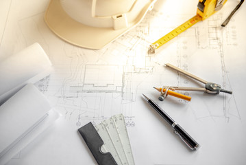 Compass tool, pen, scale, tape measure and safety helmet on architectural drawing plan of house project, blueprint rolls on working table, Architecture and building construction industry concepts