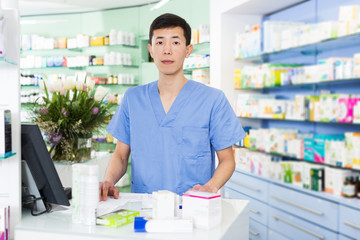 japanese specialist standing near table with cashbox in pharmacy