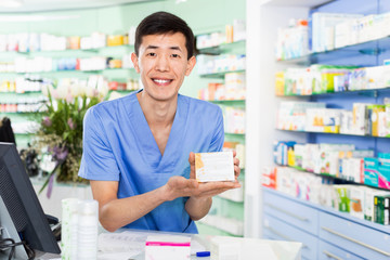 Portrait of chinese man pharmacist who is standing on his work place near cashbox in apothecary.