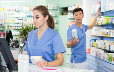 Positive pharmacist is standing near cashbox