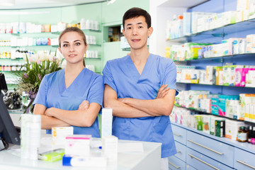 Portrait of two pharmacists who are standing on their work place near table with cashbox in apothecary.