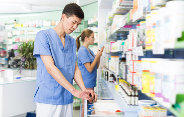 Glad japan man is searching medicines on shelves