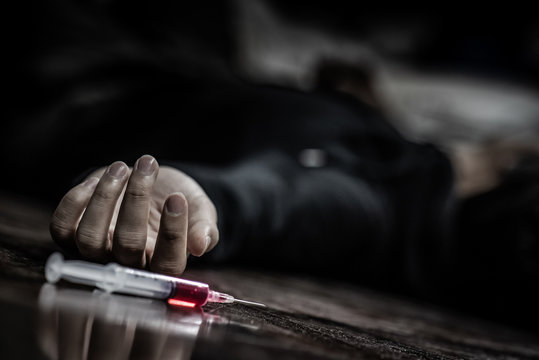 Junkie man lying on the floor near drug injection syringe. Death from drug overdose and addiction concept