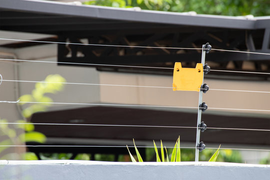high voltage security fence on house wall with blank yellow plastice sign.