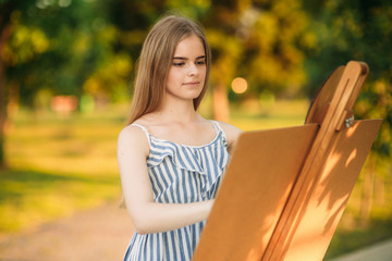 Blond hair girl in dress drawing a picture in the park