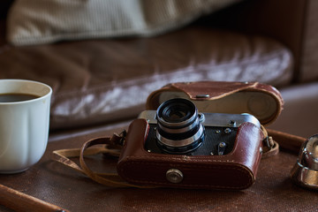 Image of retro camera and vary of decoration on wooden table background. Vintage color tone.