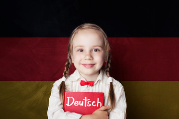 Learning german language concept with happy child girl and german flag background