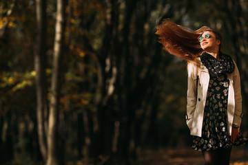 Cheerful girl outdoors enjoying nature. Beautiful autumn hair model with waving glow hair. Photo in motion.