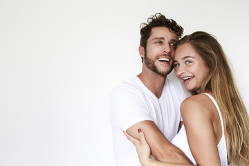 Laughing young couple in white studio, portrait