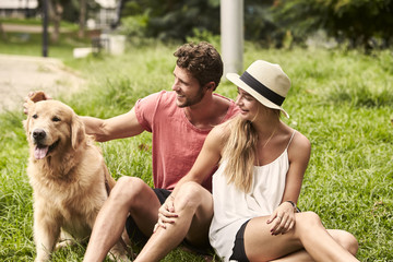 Young couple petting pooch in city park, brazil