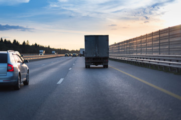 Highway traffic in sunset. road with metal safety barrier or rail. Truck on the asphalt road. Sound acoustic barrier on the right side