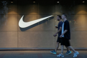 Men walk past a Nike store in central Kiev