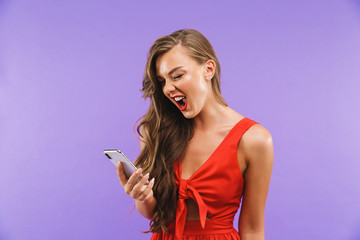 Image closeup of happy cheerful woman 20s wearing red dress screaming and holding mobile phone, standing isolated over violet background