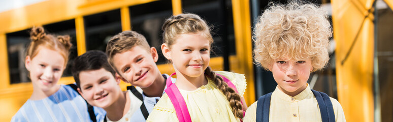 panoramic shot of group of adorable pupils looking at camera while standing in row in front of school bus