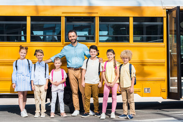 schoolchildren and teacher standing together in front of school bus and looking at camera