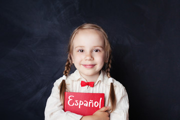 Beautiful child girl smiling and holding book in spanish language school. Learning spanish