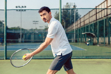 Portrait of determined tennis player looking forward with concentration before serving during a challenging match