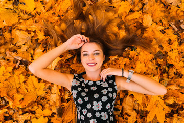 Beautiful and cute girl with long hair in autumn park on the sunny day lying in a big pile of leaves, top view