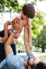 Dad lifting son in park, smiling