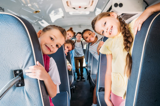 group of cute schoolchildren riding on school bus and looking at camera