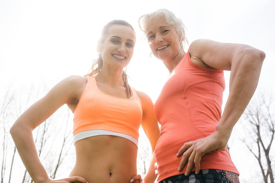 Senior and young woman doing sport outdoors looking down