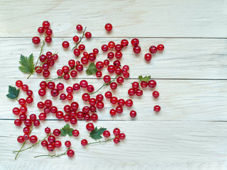 Large red currant berries are scattered on a wooden background