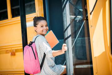 happy little schoolgirl entering school bus and looking at camera