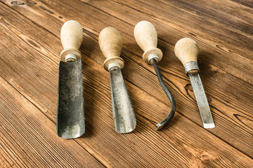 Cutters for wood carving, on a wooden background, close-up, cutting tool