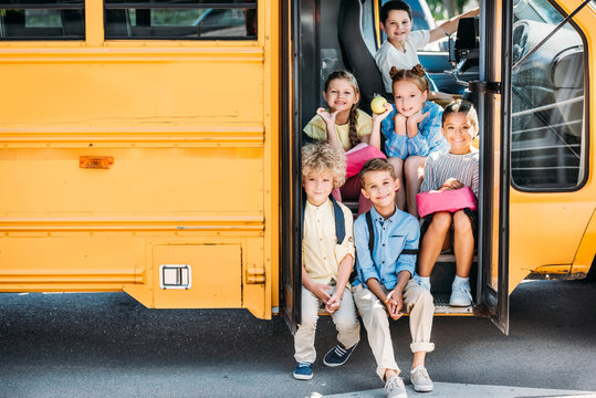 group of adorable schoolchildren sitting on stairs of school bus and looking at camera