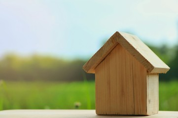 miniature wood house on green background with sunlight.Dream home with nature,mini icon.