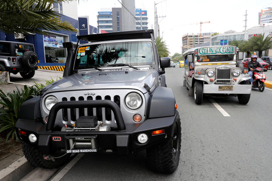 A Philippine made passenger jeepney drives past a U.S. made Jeep Wrangler SUV outside a local dealer of U.S. made vehicles, Automotive Icon in Alabang