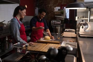 Chefs preparing dough in kitchen