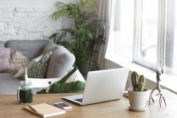 Workplace of modern freelancer leading healthy lifestyle: open generic laptop computer, cactus in pot, smart phone, copybook and glass of green smoothie on wooden desk in stylish home office interior
