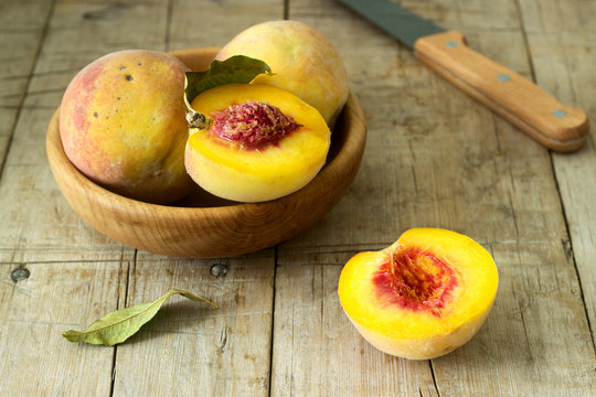Three ripe velvet peaches in a wooden bowl on a wooden background. Rustic style.