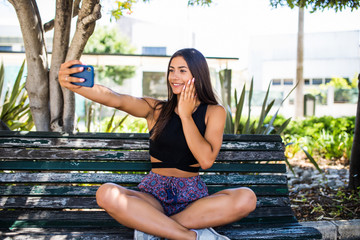 Young latin girl getting a selfie on a wooden bench in city street