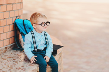 Happy smart kid in glasses is going to school for the first time. Child boy with bag go to elementary school. Child of primary school