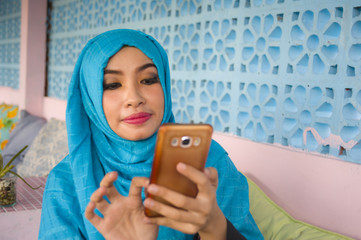 lifestyle outdoors portrait of young happy and beautiful woman in muslim hijab head scarf using internet social media app on mobile phone sending text