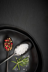 Salt in mixed pepper in vintage spoons on old metal plate with linen napkin on dark grey stone, space
