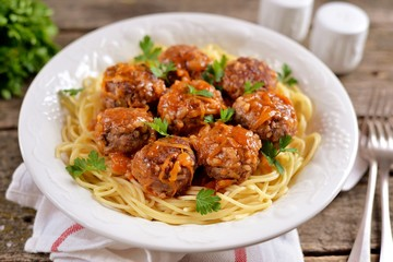 Meatballs with rice, onions, carrots with spaghetti in tomato sauce. Rustic style, rustic food on an old wooden background.