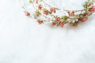soft focus handmade floral tiara made of rose flowers on white fur background with copy space. hand crafted decorative fashion accessories. artificial flowers crown.