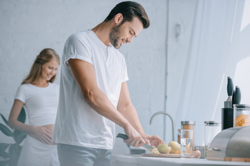 selective focus of man cutting fruits at counter with pregnant wife behind in kitchen at home
