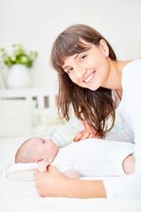 Glückliche Mutter füttert Baby mit Milch