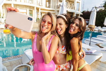Three cheerful young women in swimwear