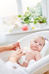 Baby wird in der Babybadewanne gebadet