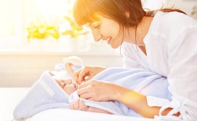Mutter beim Abtrocknen von Baby nach Bad