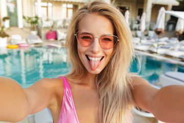 Cheerful young woman in swimsuit, sunglasses