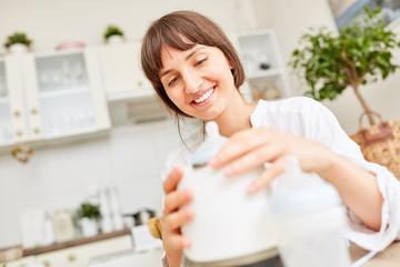 Mutter beim Erwärmen von Babymilch