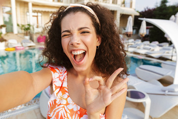 Happy young woman in swimsuit taking a selfie