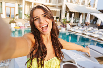 Excited young woman in swimsuit taking a selfie